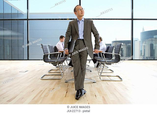 Pensive businessman holding laptop in conference room