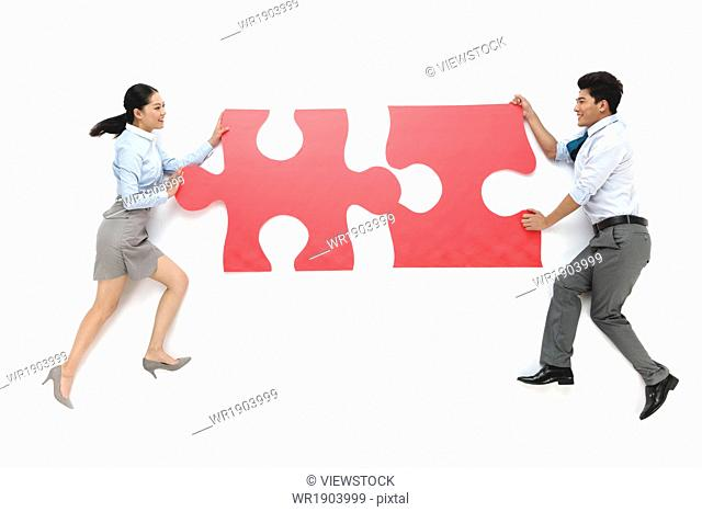 Business men and women carrying puzzle pieces