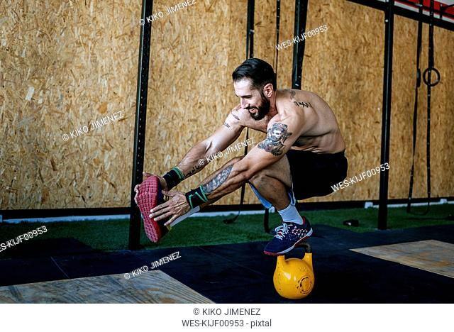 Man keeping balance on a kettlebell in gym
