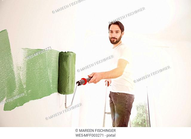 Young man painting a wall green