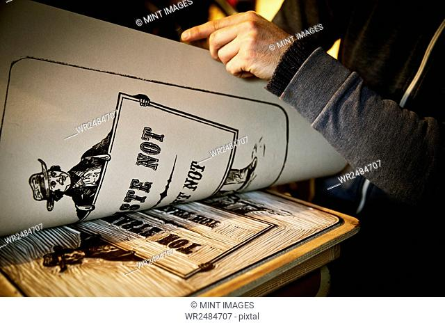 A sign writer lifting a sheet of imprinted card off a cut-out linoleum surface, a woodcut