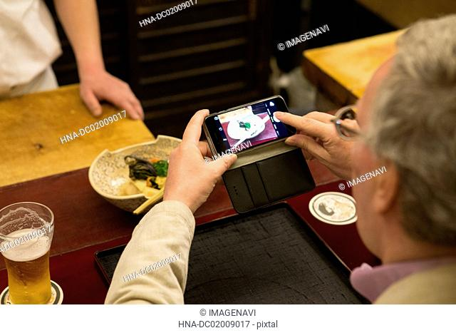 Mature Caucasian man taking photo for dishes