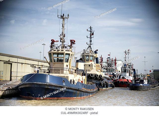 Tug boats docked in urban harbor
