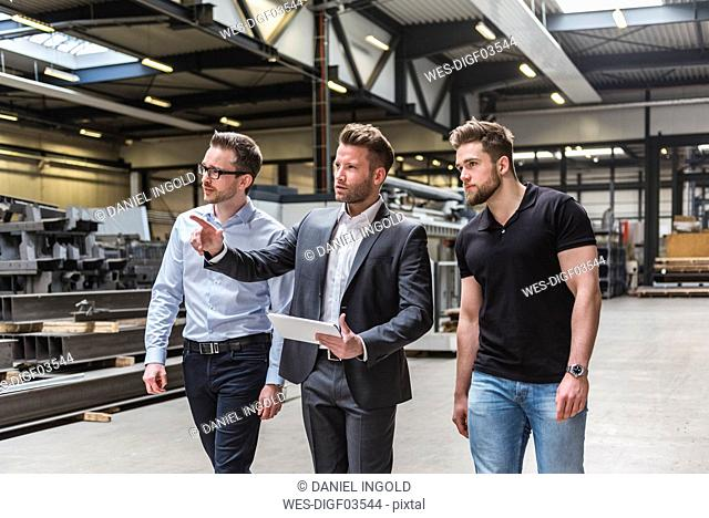 Three men with tablet walking and talking on factory shop floor