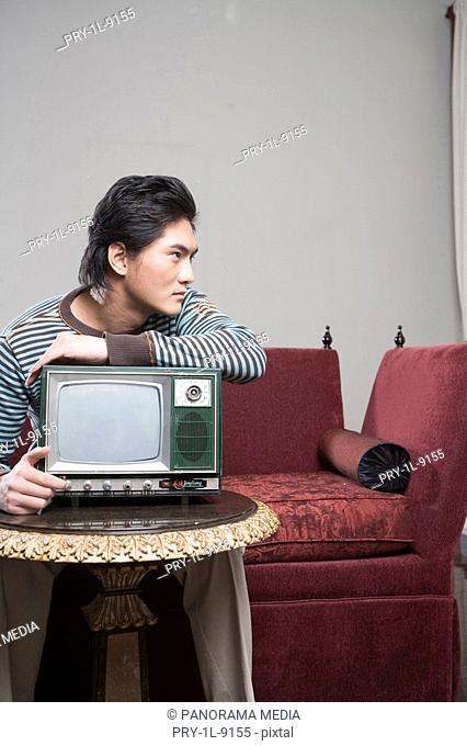 a gentleman holding an old TV