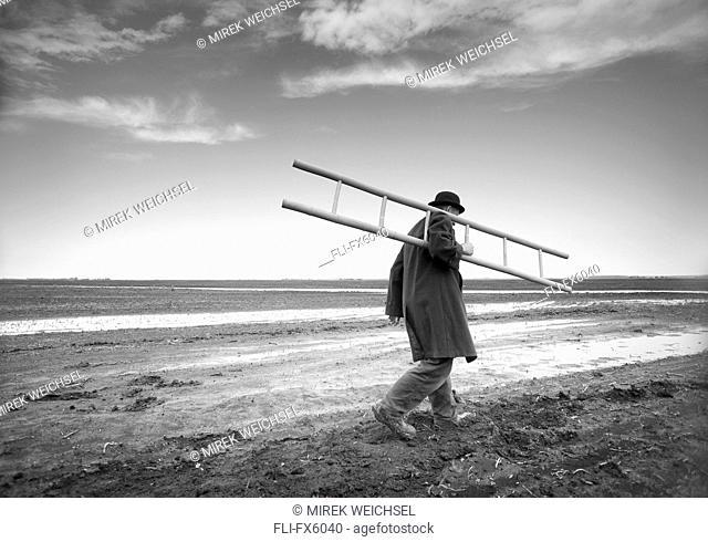 Man Carrying Ladder in Muddy Field, Winnipeg, Manitoba
