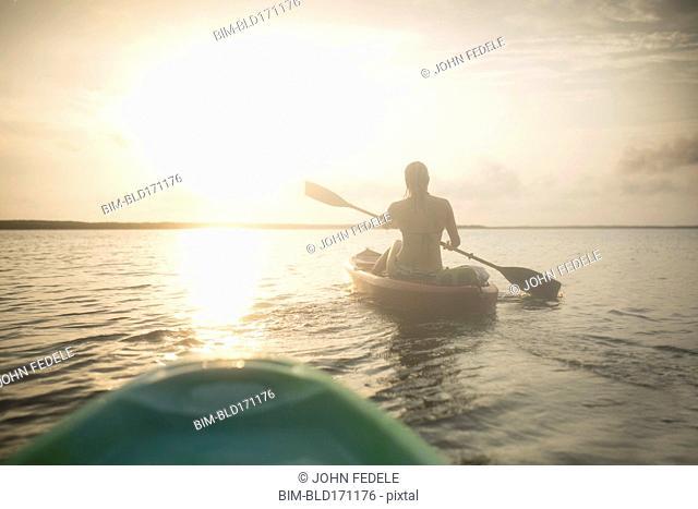 Caucasian woman rowing canoe on still lake