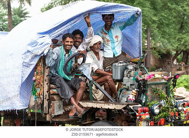 Rickety truck carrying a group of people on a rainy day, Rajasthan, India