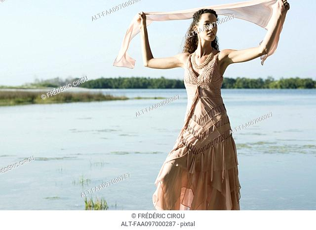 Young woman wearing dress, holding up scarf, lake in background