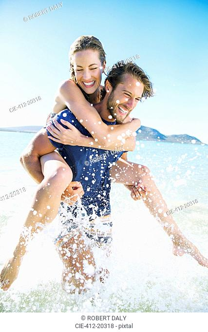 Woman riding piggy back on boyfriend in water