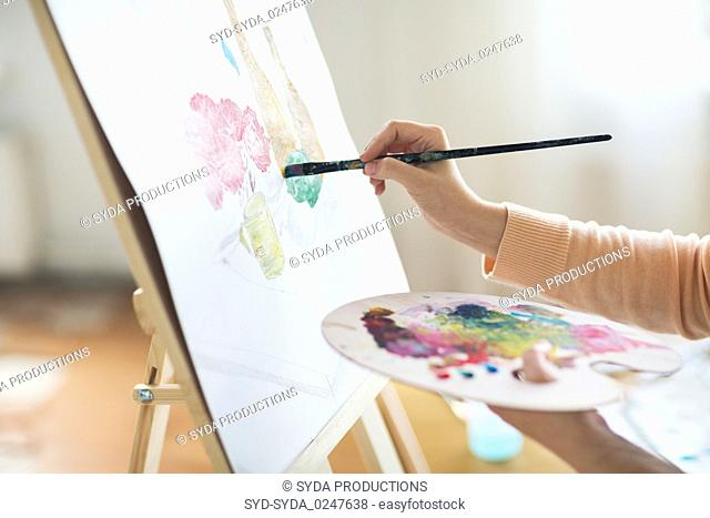 artist with palette painting at art studio