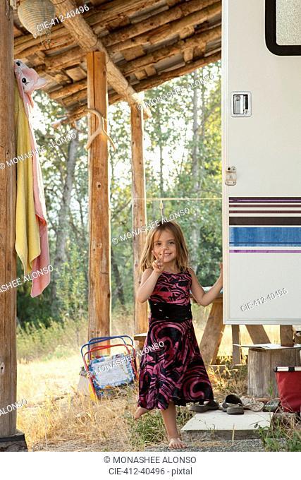 Portrait smiling, confident girl in dress gesturing peace sign outside rural camper