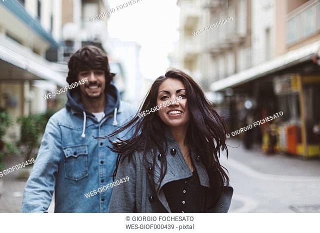 Italy, Rimini, smiling couple in the city
