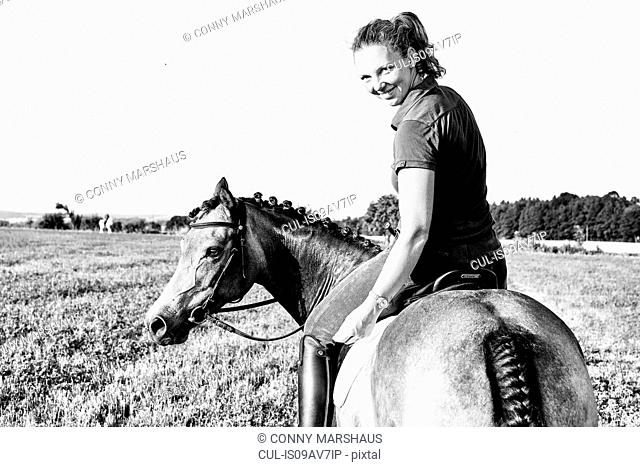 B&W portrait of woman riding horse in field and looking over her shoulder