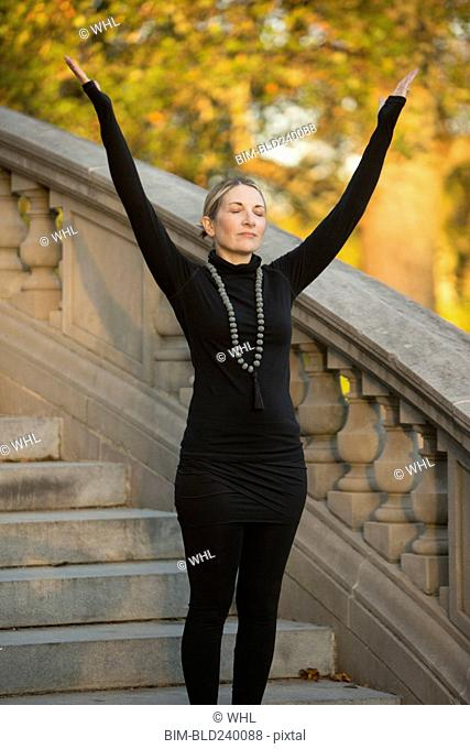 Caucasian woman meditating on staircase in park