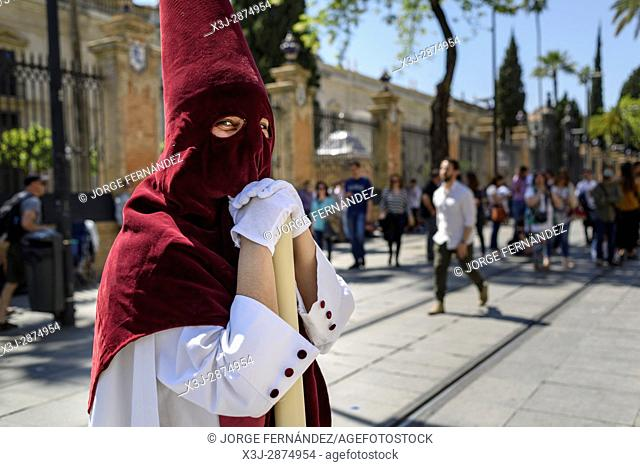 Portrait of a Nazarene penitent with red hood and white robes participating in a procession