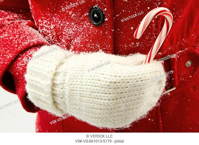 Girl (12-13) holding candy cane