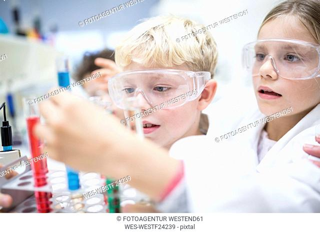 Pupils in science class experimenting with liquids in test tubes