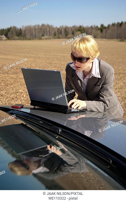 Businesswoman Using Laptop Computer on Car Bonnet by Field