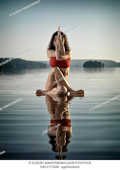 Artistic concept of a young woman in swimsuit doing a variation of yoga Eagle posture, Guradasana, meditating on a floating platform in water on the lake in...