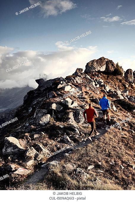 Trail runners on rocky path, Valais, Switzerland