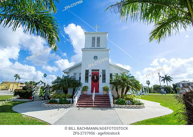 Everglades City Florida Everglades Community Church founded in 1926 in small village steeple and palms with red door