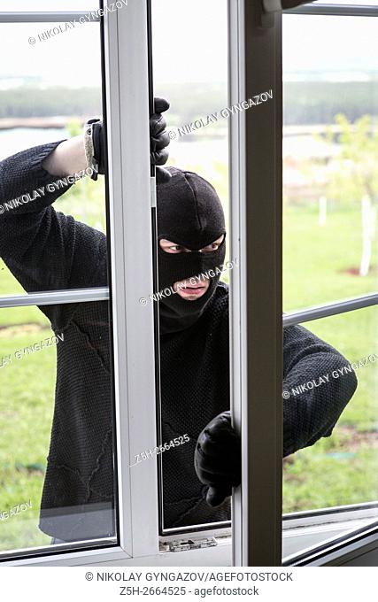 Russia. A criminal in a black mask breaks apartment window