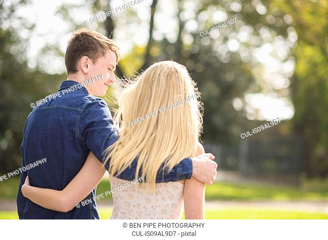 Rear view of romantic young couple strolling in park