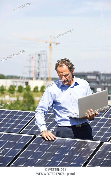 Germany, Munich, Mature man with laptop in solar plant