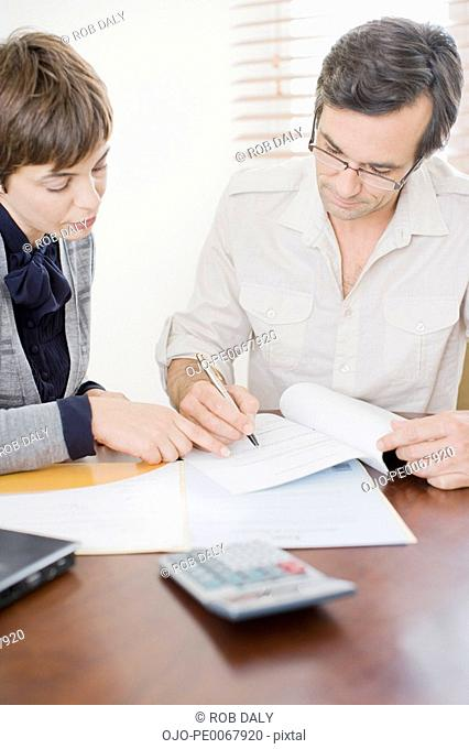 Businesswoman guiding man with paperwork