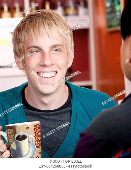 Man in coffee house with male friend