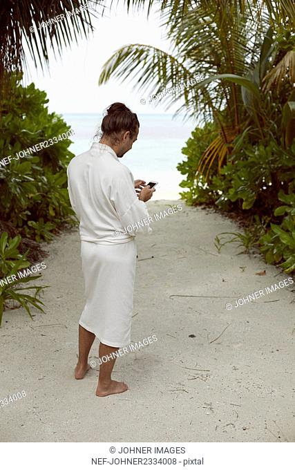 Man wearing dressing gown on beach