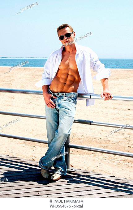 Sexy handsome male with sunglasses and toned body showing six pack abs with white shirt open while standing next to railing on boardwalk at beach
