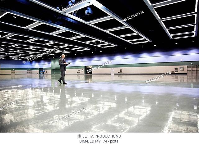 Caucasian businessman walking in empty convention center