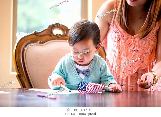 Baby boy with American flag, crayon drawing at dining room table