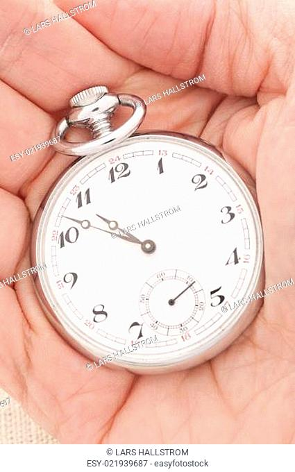 Hand holding an old pocket watch
