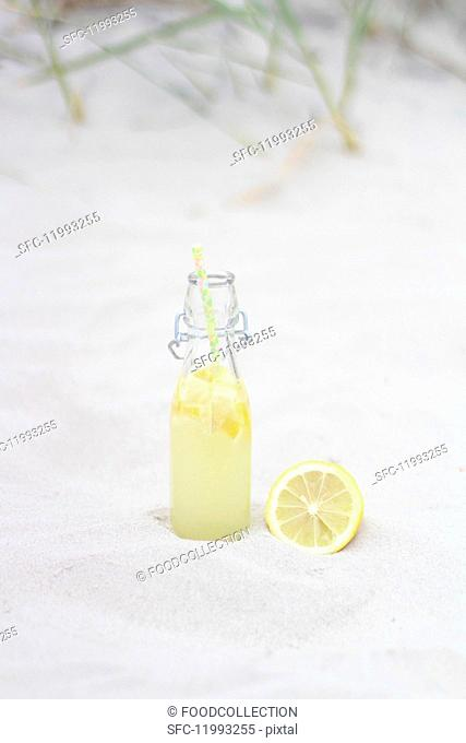 A bottle of lemonade with a lemon in the sand
