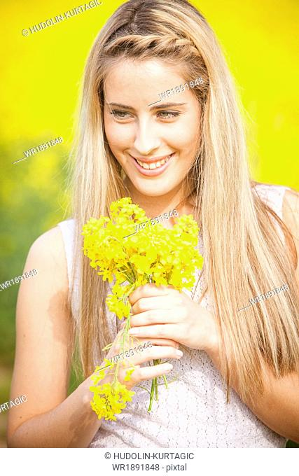 Blonde woman holding bunch of colza flowers, Tuscany, Italy
