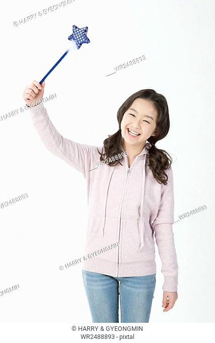 Smiling middle school girl in casual clothes holding a wand