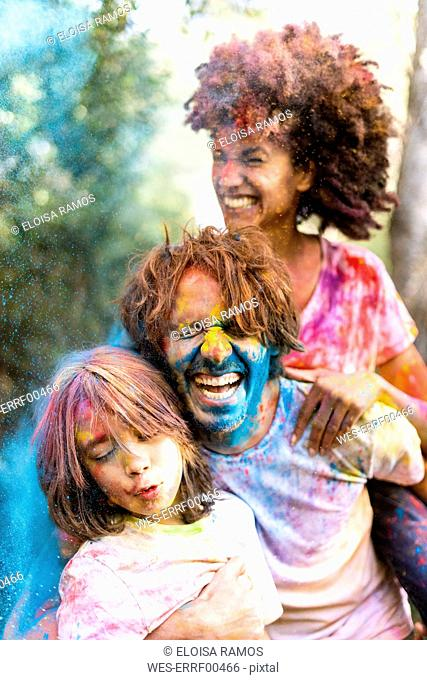 Family full of colorful powder paint, celebrating Holi, Festival of Colors