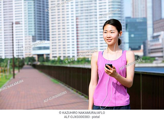 Young Japanese woman with smartphone before her run downtown Tokyo