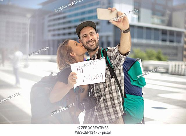 Couple with backpack taking a selfie in the city