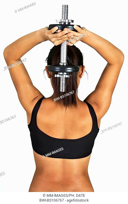 athletic Asian woman training her shoulder muscles with a dumb bell