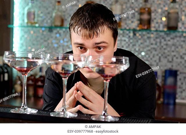 Attractive young man bending down and checking out three glasses of cocktail standing on a bar counter at a hotel or nightclub