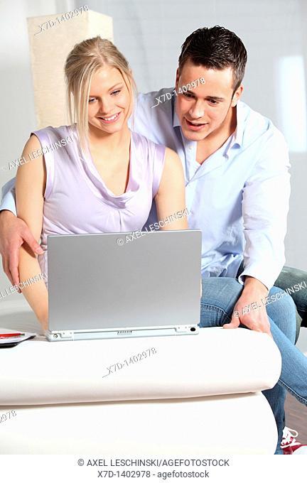 man teaching woman on laptop