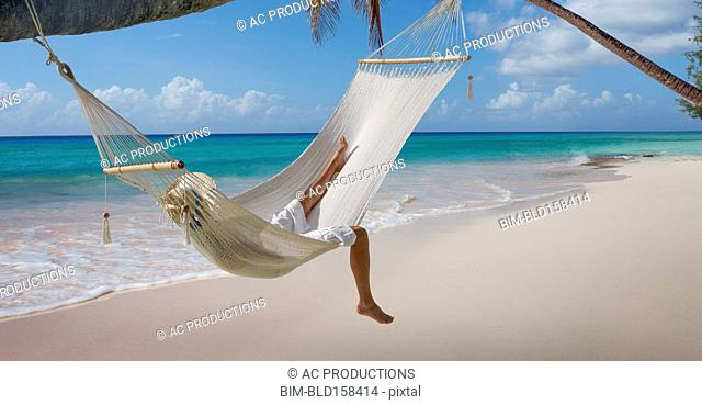 Caucasian woman laying in hammock on tropical beach