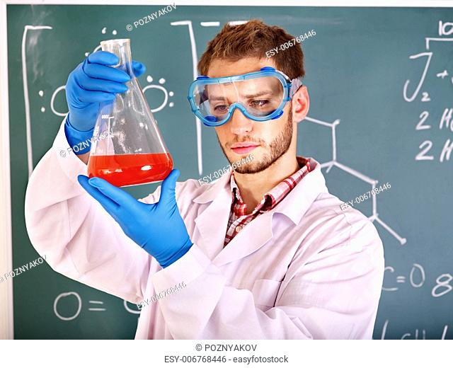Man chemistry student with flask in classroom