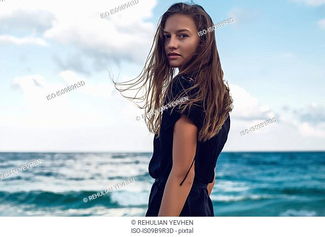 Portrait of young woman looking over her shoulder on beach, Odessa, Odessa Oblast, Ukraine