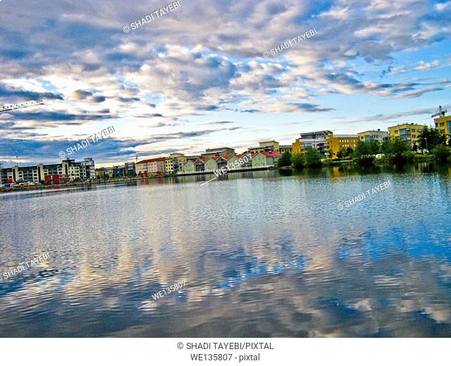 Sea and the reflection of clouds in the water, apartments in the background in a city called Jönköping, Sweden