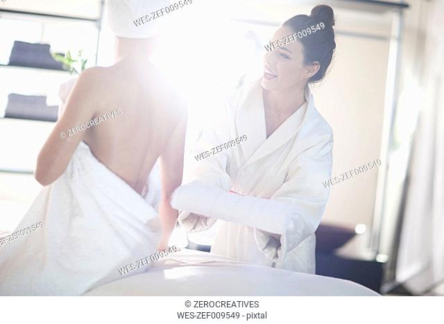 Young woman laying down on massage table in spa